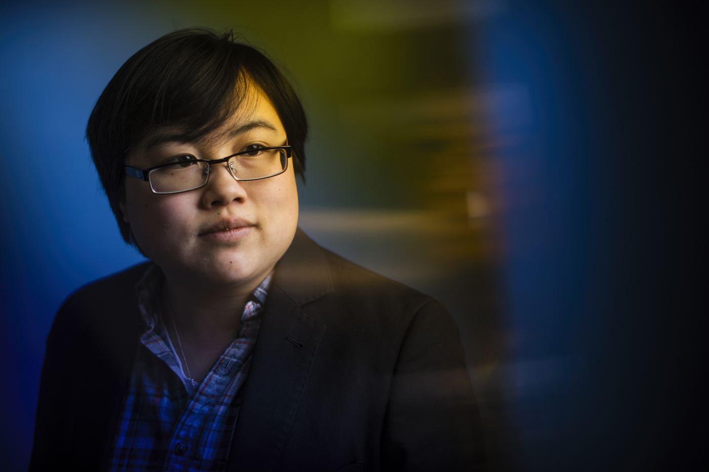 [Photo: Headshot of Lydia Brown, young East Asian person, with stylized blue and yellow dramatic background. They are looking in the distance and wearing a plaid shirt and black jacket. Photo by Adam Glanzman.]